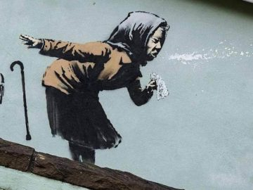 """The elusive British street artist's piece — titled """"Aachoo!!"""" — depicts an elderly woman sneezing, sending her dentures flying out of her mouth."""